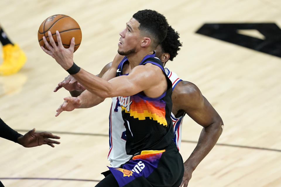 Phoenix Suns guard Devin Booker (1) shoots against Philadelphia 76ers during the second half of an NBA basketball game, Saturday, Feb. 13, 2021, in Phoenix.(AP Photo/Matt York)