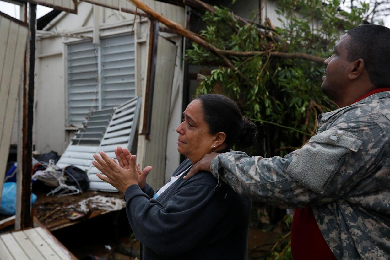 A woman reacts while she looks at the damages in the house of her mother in Guayama.