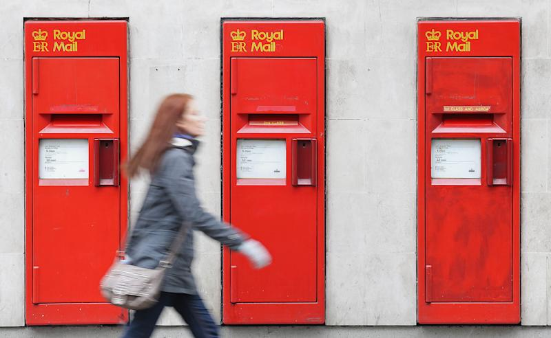 FILE - This is a June 19, 2013 file photo of a pedestrian as she walks past post boxes in London. The British government laid out plans Wednesday July 10, 2013 to privatize the Royal Mail in a 3 billion pound ($4.5 billion) share offering that will see tens of thousands of workers get a stake in the company. The government plans to retain a stake, opening the possibility it will sell more shares in the future. (AP Photo/Philip Toscano/PA, File) UNITED KINGDOM OUT