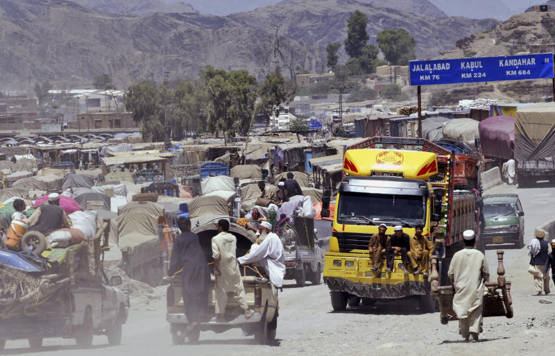 People sit on top of vehicles waiting to cross the border from Pakistan to Afghanistan in Torkham, Pakistan, Wednesday, May 23, 2012. (AP Photo/Mohammad Sajjad)