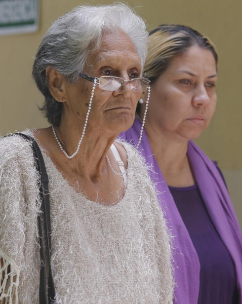 Carmen Arevalo de Acosta, left, and Carmen Acosta, mother and sister of Navy Captain Rafael Acosta walk out of the morgue in Caracas, Venezuela, Wednesday July 10, 2019. Rafael Acosta, a Venezuelan navy captain who died of suspected torture while in government custody, was buried by authorities against the family's wishes to perform a private ceremony, an attorney and relatives said. (AP Photo/Leonardo Fernandez)