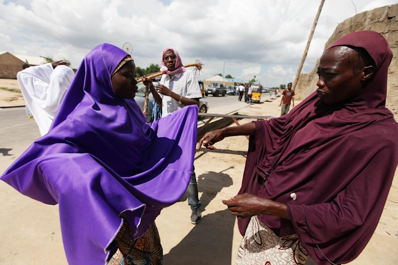 FILE - In this Wednesday, Aug. 7, 2013 file photo, Habiba Saadu, right, 48, a member of the vigilante force dubbed the Civilian JTF, searches a woman under her veil at a check point in Maiduguri, Nigeria. In an area of Nigeria where an Islamic insurgency has caught fire, security forces are carrying out night raids in residential neighborhoods and have arrested many people. Saadu's two sons and her daughter were taken Aug. 3 by soldiers who went from house to house in a night raid in Maiduguri, the capital of Borno state, accusing them of participating in the uprising by Boko Haram, an armed Islamic group that has been waging a bloody war in Africa's most populous nation for four years. (AP Photo/Sunday Alamba, File)