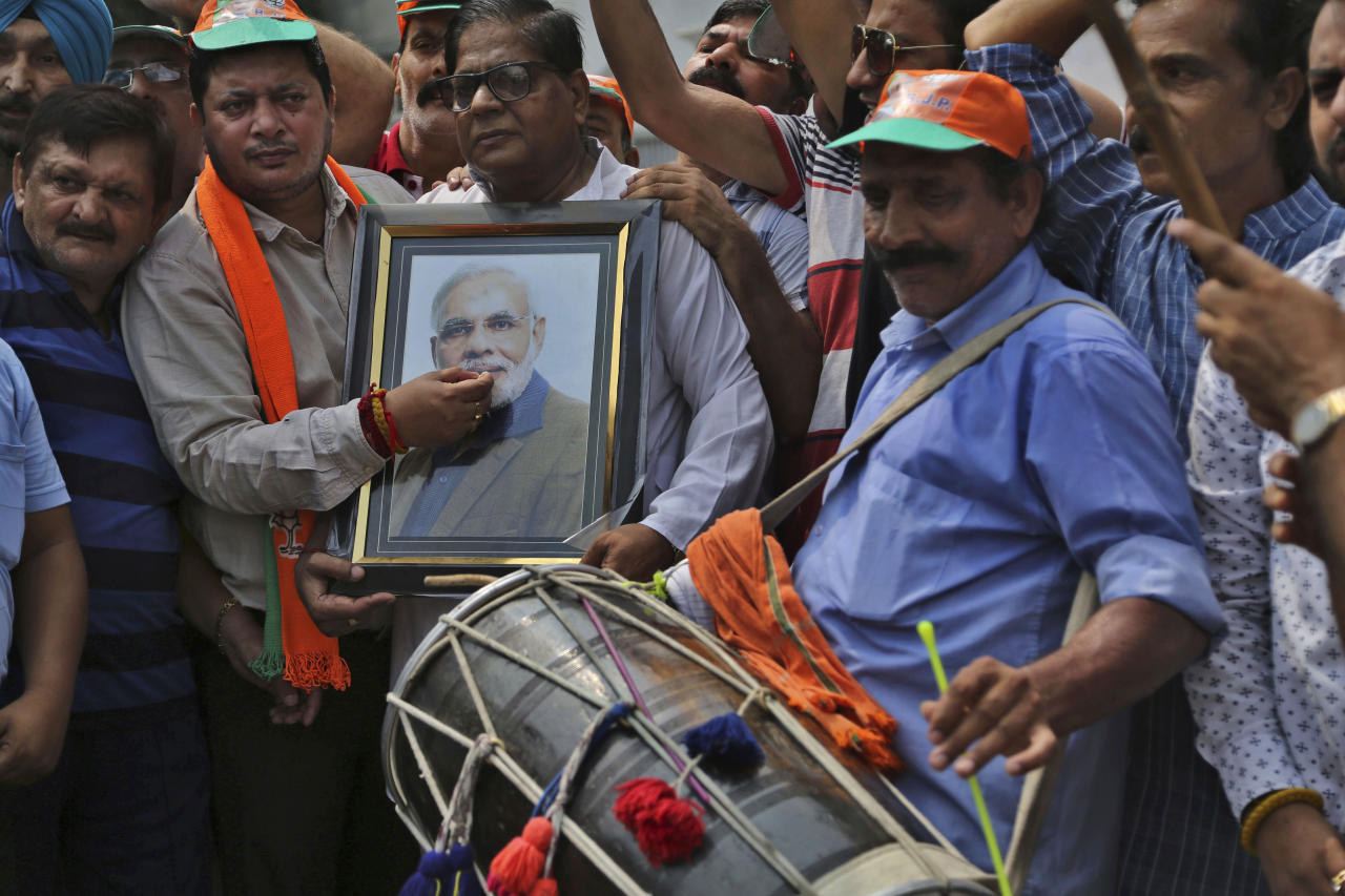 Supporters of India's ruling Bharatiya Janata Party (BJP) celebrate the government revoking Kashmir's special status in Jammu, India,Tuesday, Aug.6,2019.(AP Photo/Channi Anand)