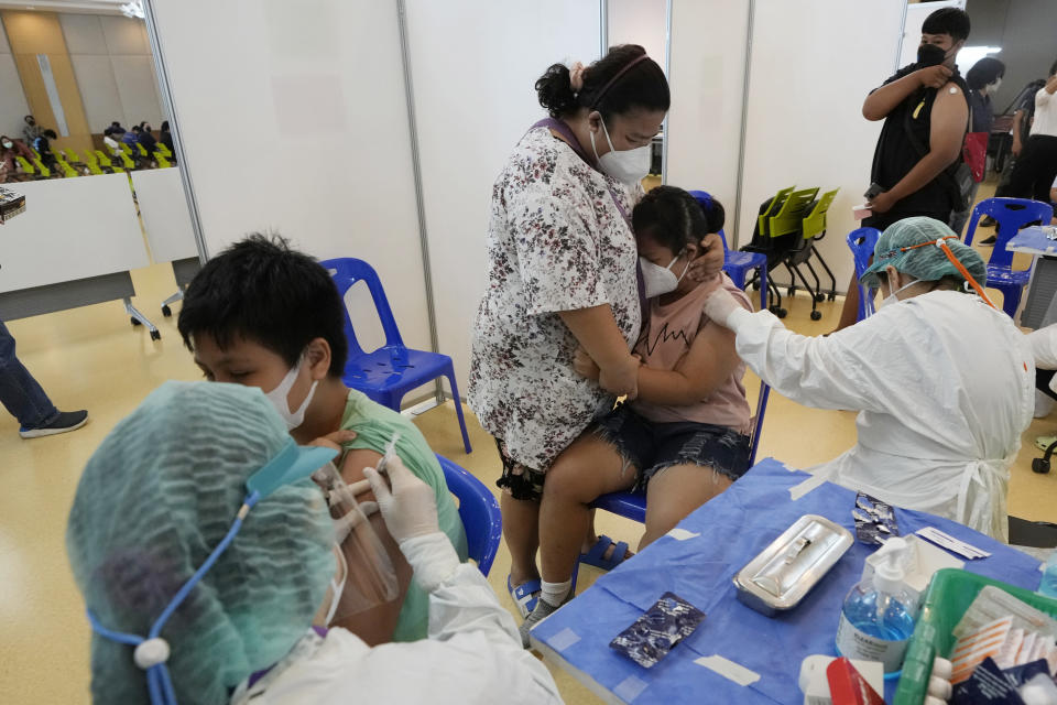 A mother tries to comfort her child before receiving the Pfizer-BioNTech COVID-19 vaccine at a hospital in Bangkok, Thailand, Tuesday, Sept. 21, 2021. Bangkok Metropolitan Administration started inoculated 12-18 year old students Tuesday as part of its attempt to reopen on-site schools. (AP Photo/Sakchai Lalit)
