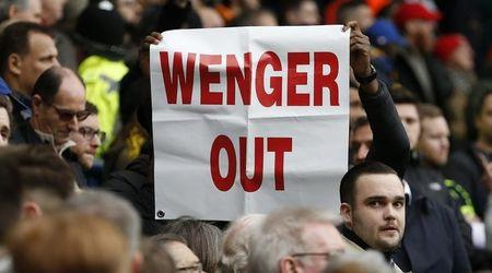 Arsenal fans hold up banners directed at manager Arsene Wenger at the end of the match