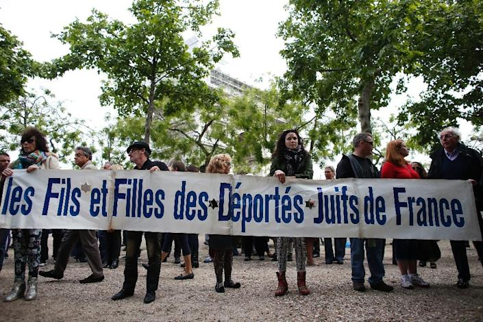 """Protestors hold a banner reading : """"Sons and Daughters of Deported French Jews"""" in front of the Belgian embassy in Paris, on May 25, 2014, to protest the killing of four people at the Jewish Museum in Brussels (AFP Photo/Thomas Samson)"""