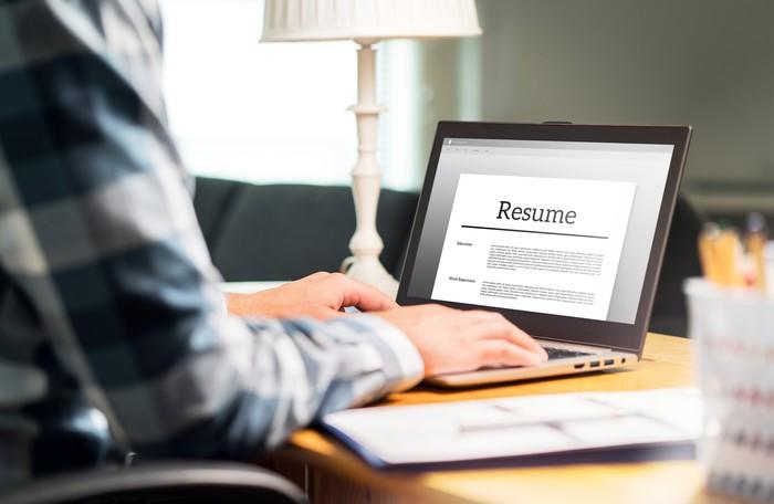 Man typing on laptop with resume open on screen