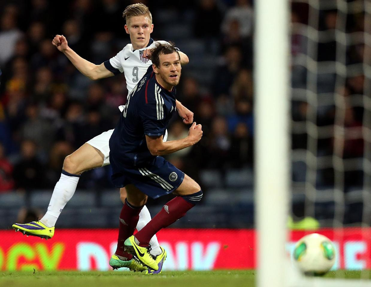 United States' Aron Johannsson, left, has a shot towards goal, unsuccessfully past Scotland's Gordon Greer, right, during their international soccer match at Hampden Park, Glasgow, Scotland, Friday Nov. 15, 2013. (AP Photo/Scott Heppell)