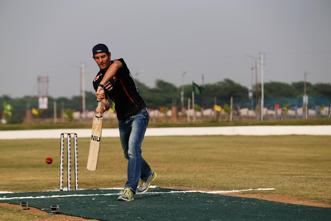 NOIDA, INDIA - OCTOBER 24:  Mark Webber of Australia and Red Bull Racing faces up to the bowling of Indian cricketer Gautam Gambhir during previews for the Indian Formula One Grand Prix on October 24, 2012 in Noida, India.  (Photo by Mark Thompson/Getty Images)