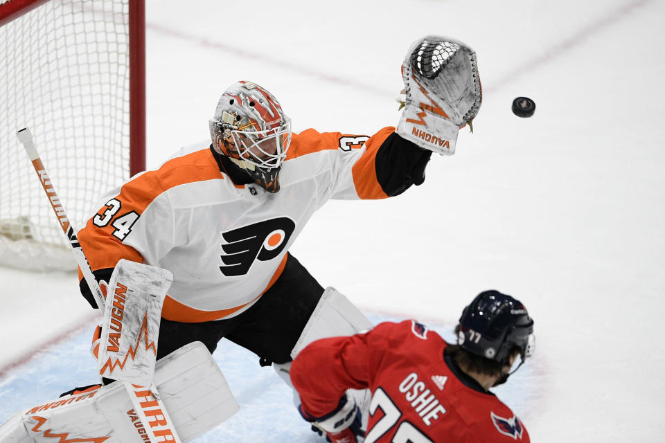Philadelphia Flyers goaltender Alex Lyon (34) prepares to catch the puck next to Washington Capitals right wing T.J. Oshie (77) during the first period of an NHL hockey game Saturday, May 8, 2021, in Washington. (AP Photo/Nick Wass)