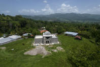 An aerial view shows the property of drug trafficker Nery Orlando Lopez Sanabria, where he is buried in the mausoleum, center, still under construction, after he was killed in a prison riot, in the Santa Barbara department of Honduras, Thursday, July 15, 2021. More than 1,000 people are stranded in this area marked by poverty and drug violence that have driven so many Hondurans to the United States. (AP Photo/Rodrigo Abd)