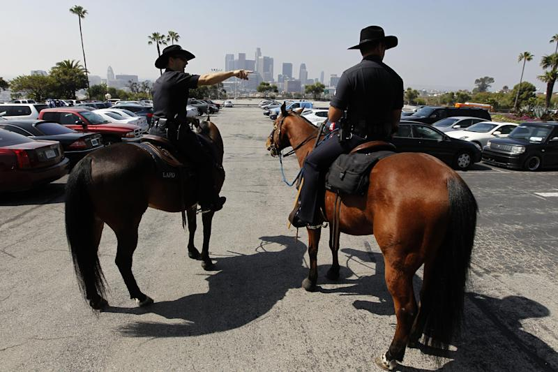 FILE - This April 10, 2012 file photo shows members of the Los Angeles Police Department's mounted patrol working the parking lot before a baseball game between the Los Angeles Dodgers and the Pittsburgh Pirates, in Los Angeles. A driver was beaten in the Dodger Stadium parking lot after a weekend game and four people were arrested on suspicion of assault with a deadly weapon, police said Monday, May 21, 2012.(AP Photo/Chris Carlson, File)
