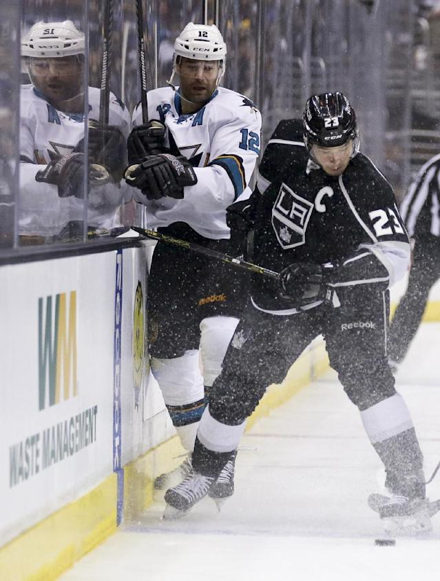 Los Angeles Kings right wing Dustin Brown, right, battles San Jose Sharks center Patrick Marleau for the puck during the first period in Game 4 of an NHL hockey first-round playoff series in Los Angeles, Thursday, April 24, 2014. (AP Photo/Chris Carlson)