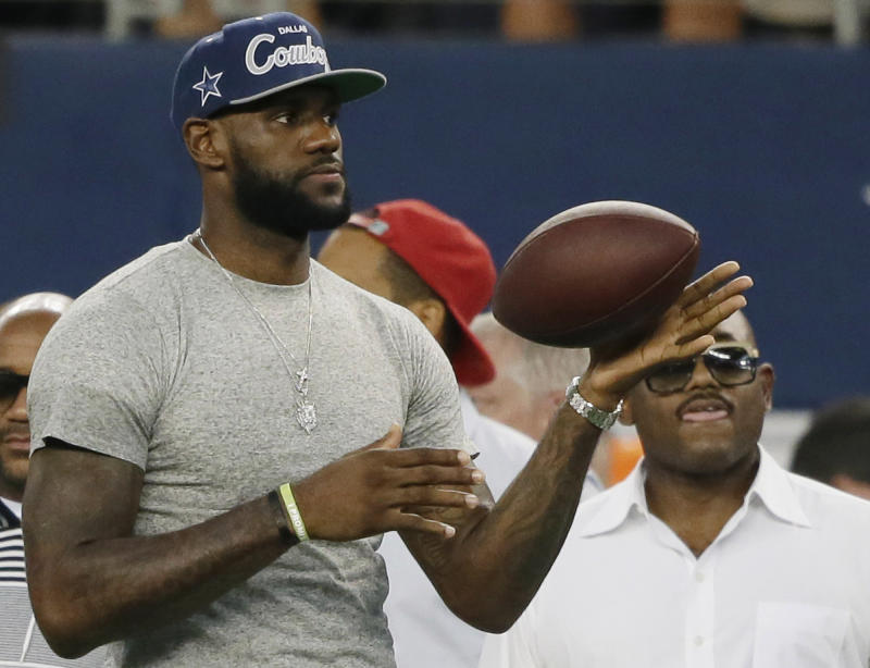LeBron James tosses a ball around before an NFL football game between the Dallas Cowboys and the New York Giants, Sunday, Sept. 8, 2013, in Arlington, Texas. (AP Photo/Tony Gutierrez)