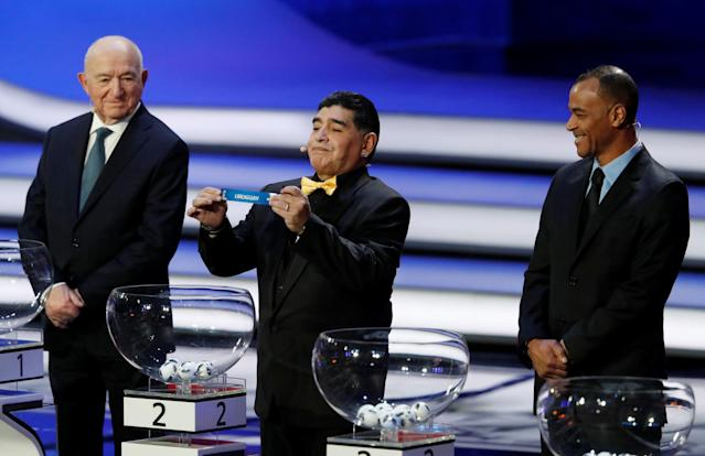 Soccer Football - 2018 FIFA World Cup Draw - State Kremlin Palace, Moscow, Russia - December 1, 2017 Diego Maradona pulls out Uruguay during the draw as Nikita Simonyan and Cafu look on REUTERS/Sergei Karpukhin