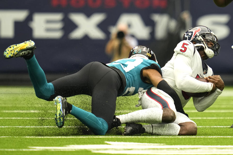 Houston Texans quarterback Tyrod Taylor (5) is sacked by Jacksonville Jaguars cornerback CJ Henderson (23) during the first half of an NFL football game Sunday, Sept. 12, 2021, in Houston. (AP Photo/Sam Craft)