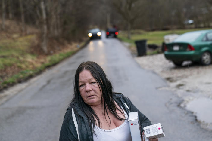 "Yvonne Ash carries back to her house a CPR kit and a supply of the overdose reversal medication naloxone after a visit from the Quick Response team, which visits everyone who overdoses to offer help, Monday, March 15, 2021, in Branchland, W.Va., just days after Ash's son overdosed, ""We need help,"" Ash said. People have been dying all around her. Her nephew. Her neighbors. Then, almost her son. ""People I've known all my life since I was born, it takes both hands count them,"" she said. ""In the last six months, they're gone."" (AP Photo/David Goldman)"