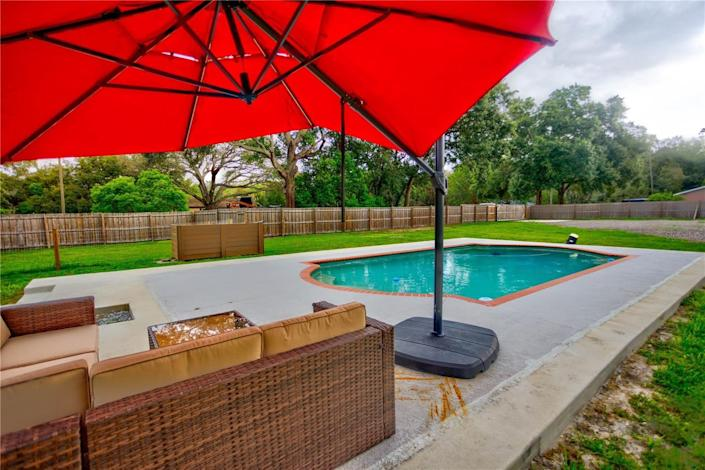 The pool and a red umbrella over outdoor couches at a house in florida