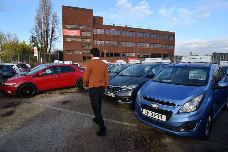 Ameen Sultani walks as he shows some of the older, cheaper vehicles that have been popular with customers eager to avoid public transport during the coronavirus disease (COVID-19) pandemic, in Hayes