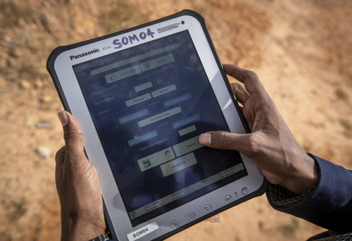 """In this photo taken Wednesday, Feb. 5, 2020, an official from the Food and Agriculture Organization (FAO) demonstrates the """"eLocust3"""" software used to record and track the location and movements of locusts using GPS and transmit the data via satellite, in the desert near Garowe, in the semi-autonomous Puntland region of Somalia. The desert locusts in this arid patch of northern Somalia look less ominous than the billion-member swarms infesting East Africa, but the hopping young locusts are the next wave in the outbreak that threatens more than 10 million people across the region with a severe hunger crisis. (AP Photo/Ben Curtis)"""