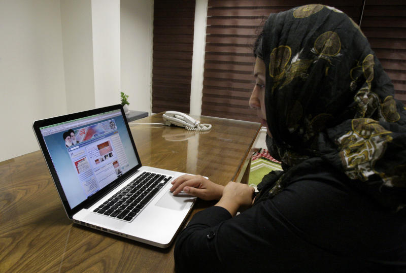Iranian photojournalist Maryam Rahmanian checks the newly launched website of Iran's Intelligence Ministry, in Tehran, Iran, Wednesday, Oct. 10, 2012. A glimpse into the shadow world of Iran's main spy agency is now a click away. In an unexpected display of outreach, the Intelligence Ministry now hosts a website with addresses of provincial offices, appeals for tips and anti-American essays that mock rising obesity rates, large prison populations and school shootings. (AP Photo/Vahid Salemi)