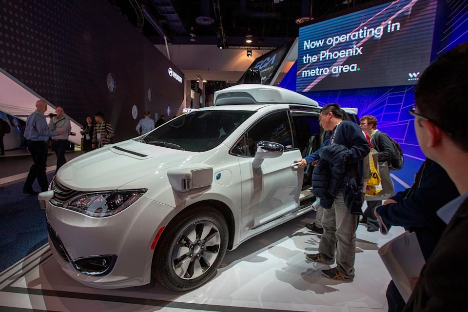 People look at the Waymo car, formerly the Google self-driving car project, during the Las Vegas Convention Center during CES 2019 in Las Vegas on January 9, 2019. (Photo by DAVID MCNEW / AFP)        (Photo credit should read DAVID MCNEW/AFP/Getty Images)
