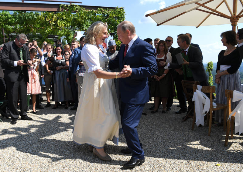 Russian President Vladimir Putin, right, congratulates Austrian Foreign Minister Karin Kneissl as he attends the wedding of Kneissl with with Austrian businessman Wolfgang Meilinger in Gamlitz, southern Austria, Saturday, Aug. 18, 2018. (Roland Schlager/pool photo via AP)