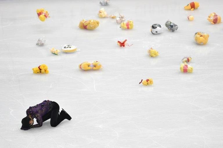 Stuffed toys thrown by fans scatter the ice rink as Japan's Yuzuru Hanyu collapses on the ice in exhaustion after performing at the Grand Prix Final