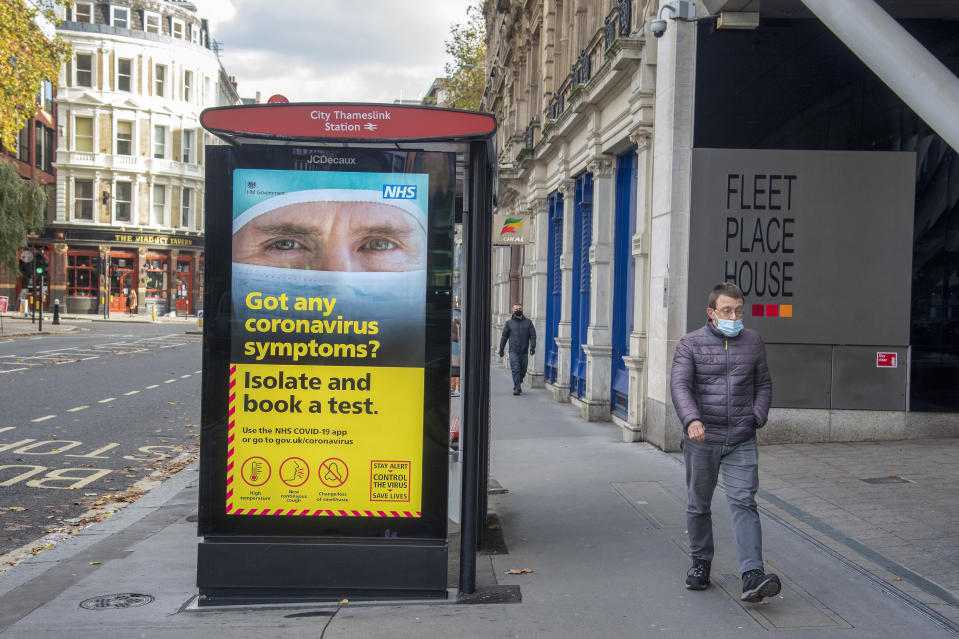 A man wearing a face mask as a precaution walking past a bus stop on an electronic display showing the NHS poster giving advice about the coronavirus testing in London. (Photo by Dave Rushen / SOPA Images/Sipa USA)