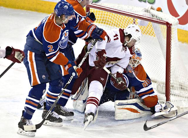 Phoenix Coyotes' Martin Hanzal (11) is pushed into Edmonton Oilers goalie Ilya Bryzgalov (80), by Jeff Petry (2) during the second period of an NHL hockey game Friday, Jan. 24, 2014, in Edmonton, Alberta. (AP Photo/The Canadian Press, Jason Franson)