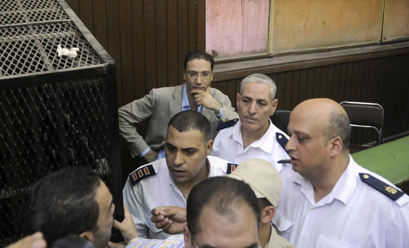 "Islam Afifi, the chief editor of el-Dustour newspaper, center, attends a court hearing in Cairo, Egypt, Thursday, Aug. 23, 2012. A Cairo court on Thursday ordered the chief editor of an Egyptian newspaper detained pending trial on charges of insulting the country's president and ""spreading lies."" The case against Afifi of the privately-owned el-Dustour daily is one of several lawsuits brought mainly by Egypt's Islamists against journalists, accusing them of inflammatory coverage and inciting the public against the Muslim Brotherhood, the country's largest political group. (AP Photo/Mohammed Asad)"