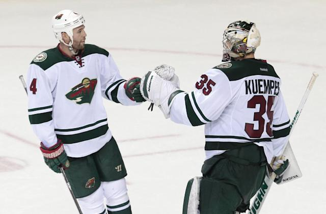 Minnesota Wild goalie Darcy Kuemper (35) is congratulated by Clayton Stoner (4) after Kuemper blocked 23 shots in a 4-0 win over the Nashville Predators in an NHL hockey game, Sunday, Jan. 12, 2014, in Nashville, Tenn. (AP Photo/Mark Humphrey)