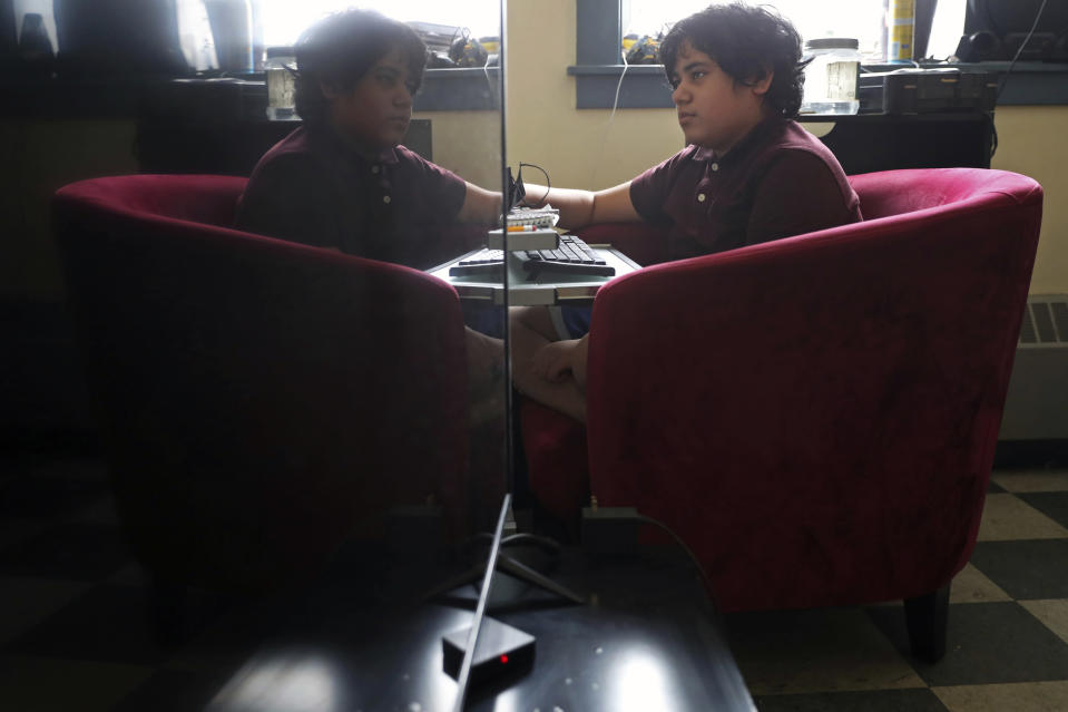 Isaias Esquivel, 12, son of Rosa Esquivel, sits in front of his computer after his virtual school hours, Wednesday, Feb. 10, 2021, at his residence in Chicago's predominantly Hispanic Pilsen neighborhood. (AP Photo/Shafkat Anowar)