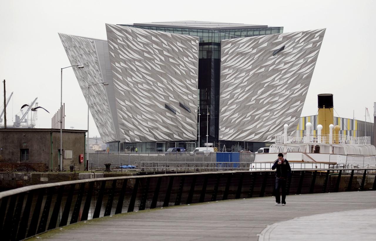 In this photo of Tuesday March 13, 2012 a man walks past the new 100 million British pounds ($157 million)Titanic Belfast Visitor's Center. Celebrating the Titanic ship and the people who built her in the Titanic Belfast, with its four prow-like wings jutting jauntily skyward beside the River Lagan on the site of the old Harland and Wolff shipyard. Titanic, then the world's largest, most luxurious ocean liner, left this spot on April 2, 1912 on its maiden voyage from England to New York, and twelve days later, it stuck an iceberg off the coast of Newfoundland and sank in the early hours of April 15, and more than 1,500 of the 2,200 people on board died. (AP Photo/Peter Morrison)