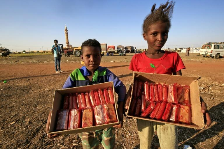 """Ethiopian children selling mini cakes in """"Village Eight"""" -- an east Sudan transit settlement that has grown into the size of a small town with the refugee influx"""