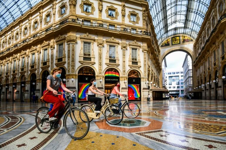 Women ride a bicycle across the Vittorio Emanuele II galleria shopping mall in Milan, as the country eases its lockdown aimed at curbing the spread of the COVID-19 infection