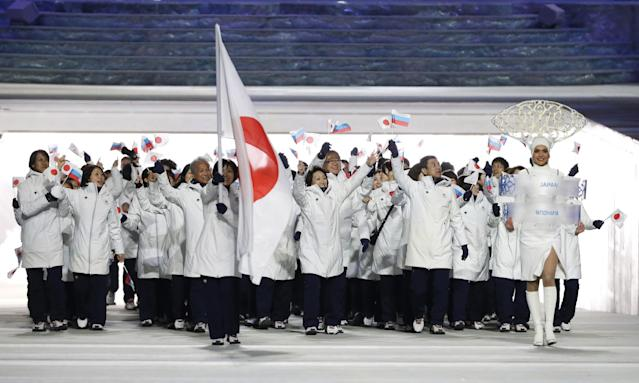 Ayumi Ogasawara of Japan carries the national flag as she leads the team during the opening ceremony of the 2014 Winter Olympics in Sochi, Russia, Friday, Feb. 7, 2014. (AP Photo/Mark Humphrey)