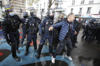 A demonstrator is pushed away by riot police officers during a banned protest in support of Palestinians in the Gaza Strip, in Paris, Saturday, May, 15, 2021. Marches in support of Palestinians in the Gaza Strip were being held Saturday in a dozen French cities, but the focus was on Paris, where riot police got ready as organizers said they would defy a ban on the protest. (AP Photo/Michel Euler)