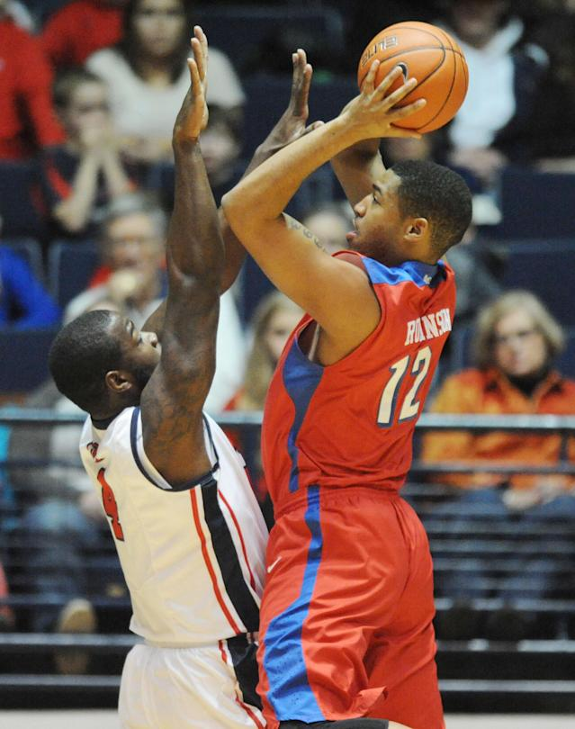 Dayton's Jalen Robinson (12) is fouled by Mississippi's Demarco Cox (4) during an NCAA college basketball game in Oxford, Miss., Saturday, Jan. 4, 2014. (AP Photo/Oxford Eagle, Bruce Newman)