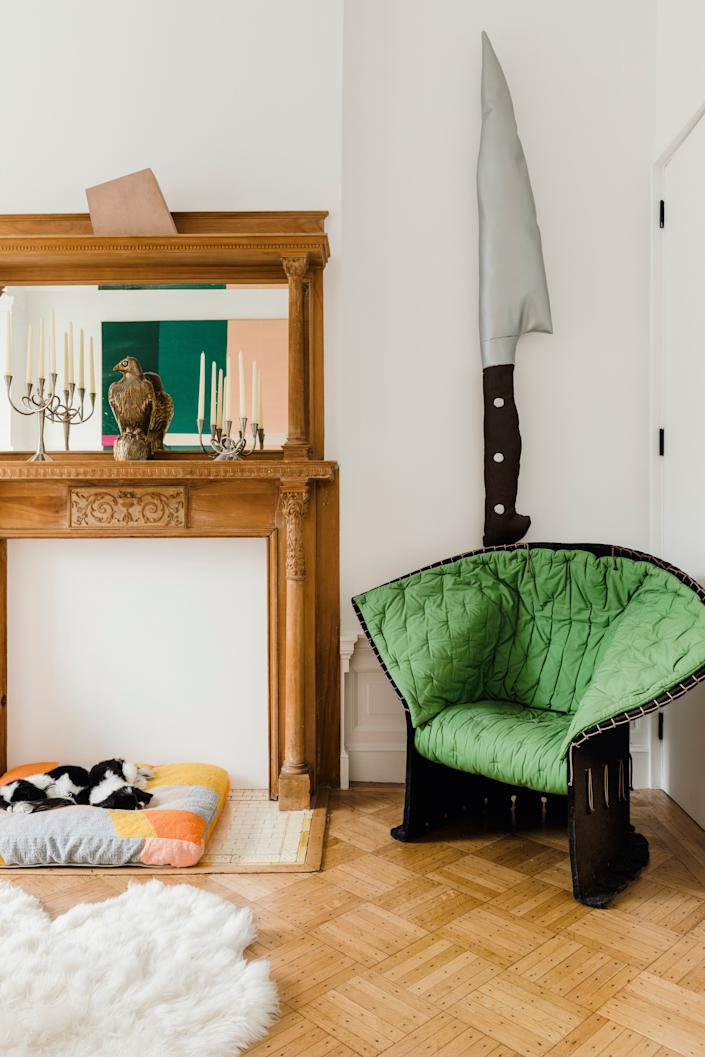 """<div class=""""caption""""> A 1987 armchair by <a href=""""https://www.architecturaldigest.com/story/at-79-design-legend-gaetano-pesce-still-has-work-to-do?mbid=synd_yahoo_rss"""" rel=""""nofollow noopener"""" target=""""_blank"""" data-ylk=""""slk:Gaetano Pesce"""" class=""""link rapid-noclick-resp"""">Gaetano Pesce</a> for <a href=""""https://www.cassina.com/en/collection/sofas-and-armchairs/357-feltri"""" rel=""""nofollow noopener"""" target=""""_blank"""" data-ylk=""""slk:Cassina"""" class=""""link rapid-noclick-resp"""">Cassina</a> sits below a knife artwork by <a href=""""https://www.artsy.net/artist/al-freeman"""" rel=""""nofollow noopener"""" target=""""_blank"""" data-ylk=""""slk:Al Freeman"""" class=""""link rapid-noclick-resp"""">Al Freeman</a> from Brussels gallery <a href=""""https://www.sorrywereclosed.com/en/expositions/presentation/109/al-freeman-loup-sarion"""" rel=""""nofollow noopener"""" target=""""_blank"""" data-ylk=""""slk:Sorry We're Closed"""" class=""""link rapid-noclick-resp"""">Sorry We're Closed</a>. Ethan's bronze hawk sculpture and candelabras by <a href=""""https://www.driade.com/en/candelabri-e-portacandele-simon"""" rel=""""nofollow noopener"""" target=""""_blank"""" data-ylk=""""slk:Borek Sipek for Driade"""" class=""""link rapid-noclick-resp"""">Borek Sipek for Driade</a> top the mantel. The couple's rescue dogs, Bishkin and Fizzgig, lounge on a bed by <a href=""""https://www.architecturaldigest.com/story/inside-ellen-van-dusens-pattern-happy-brooklyn-brownstone?mbid=synd_yahoo_rss"""" rel=""""nofollow noopener"""" target=""""_blank"""" data-ylk=""""slk:Dusen Dusen"""" class=""""link rapid-noclick-resp"""">Dusen Dusen</a> below. The concrete piece above the mantel, titled <em>Betoni</em>, is by German artist <a href=""""https://www.artsy.net/artist/imi-knoebel"""" rel=""""nofollow noopener"""" target=""""_blank"""" data-ylk=""""slk:Imi Knoebel"""" class=""""link rapid-noclick-resp"""">Imi Knoebel</a>. </div>"""
