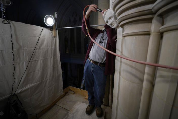 Stone carver Sean Callahan uses an air chisel during work on a sculpture of Holocaust survivor and Nobel Peace Prize winning author Elie Wiesel in the Human Rights Porch at the Washington National Cathedral, Thursday, March 25, 2021. (AP Photo/Carolyn Kaster)