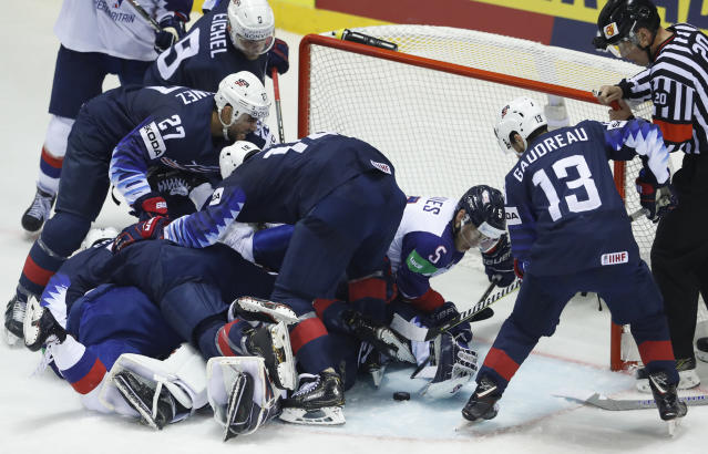 Great Britain's Ben Davies, 2nd right, reaches for the puck during the Ice Hockey World Championships group A match between the United States and Great Britain at the Steel Arena in Kosice, Slovakia, Wednesday, May 15, 2019. (AP Photo/Petr David Josek)