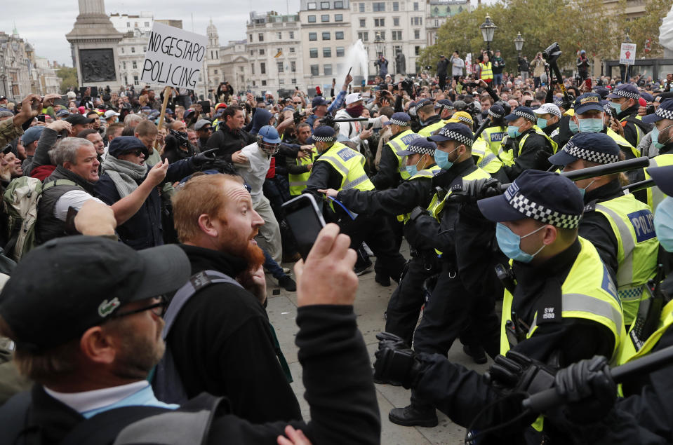 FILE - In this Sept. 26, 2020 file photo riot police face protesters who took part in a 'We Do Not Consent' rally at Trafalgar Square, organised by Stop New Normal, to protest against coronavirus restrictions, in London. (AP Photo/Frank Augstein, File)