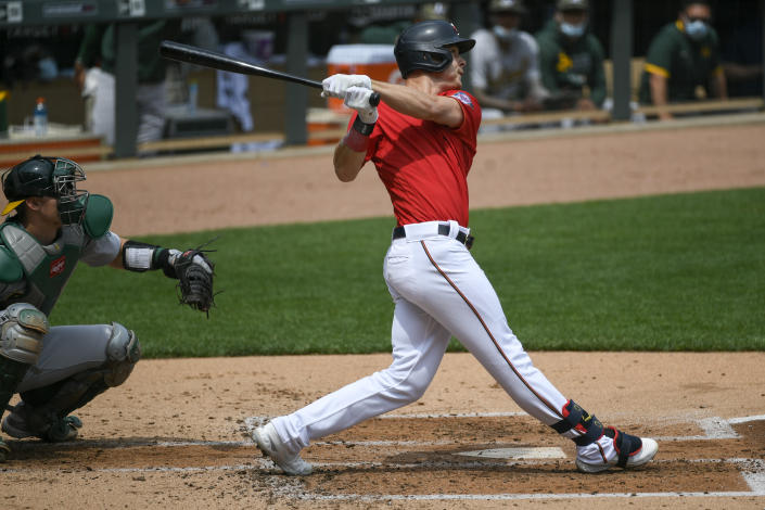 Minnesota Twins Max Kepler hits a three-run home run as Oakland Athletics catcher Sean Murphy looks on during the second inning of a baseball game, Sunday, May 16, 2021, in Minneapolis. (AP Photo/Craig Lassig)