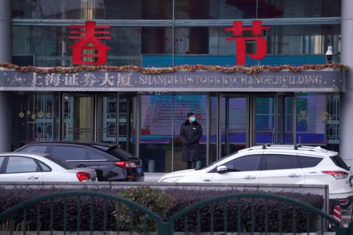 A security guard stands at the Shanghai Stock Exchange building at the Pudong financial district in Shanghai