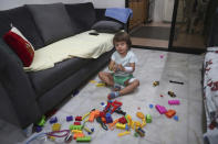 CORRECTS THE FAMILY NAME OF THE BOY - Three-year-old Abed Itani, plays with toys at his family house in Beirut, Lebanon, Tuesday, Aug. 11, 2020. Abed was playing with his Lego blocks when the huge blast ripped through Beirut, shattering the nearby glass doors. He had cuts on his tiny arms and feet, a head injury, and was taken to the emergency room, where he sat amid other bleeding people. (AP Photo/Bilal Hussein)