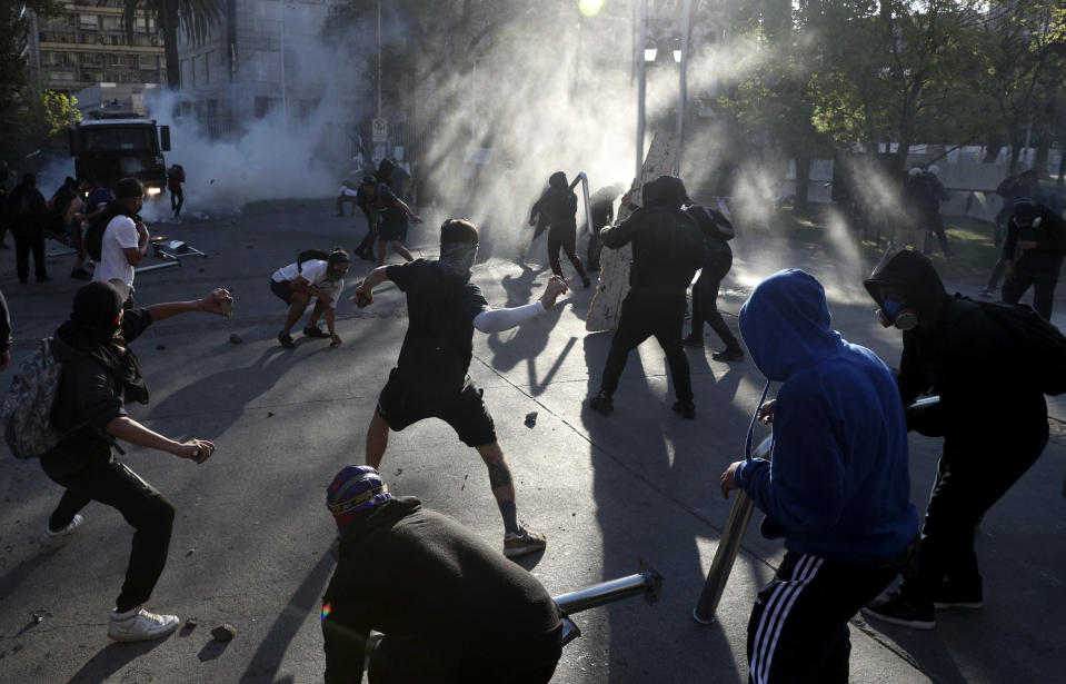 Demonstrators confront an armored vehicle during a protest against police in reaction to a video that appears to show an officer pushing a youth off a bridge the previous day at a protest, in Santiago, Chile, Saturday, Oct. 3, 2020. (AP Photo/Esteban Felix)