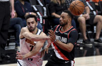 Denver Nuggets guard Facundo Campazzo, left, passes the ball on Portland Trail Blazers forward Norman Powell, right, half of Game 4 of an NBA basketball first-round playoff series in Portland, Ore., Thursday, May 29, 2021. (AP Photo/Steve Dykes)