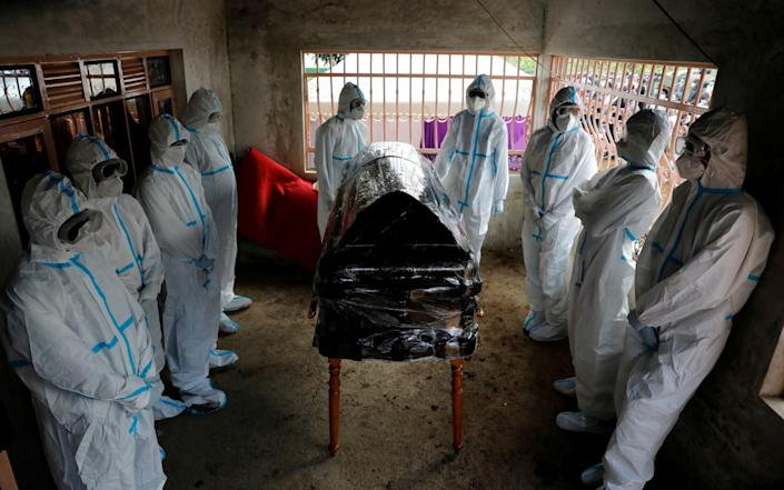 Men dressed in protective suits stand around the coffin of Kenyan doctor Daniel Alushula, who died of coronavirus, during his funeral in the village of Khumusalaba - Reuters