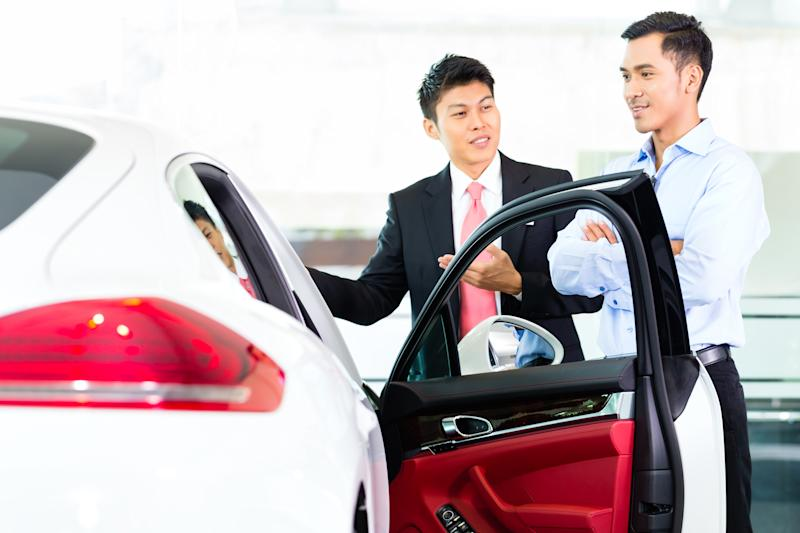 Two men stand outside a car.